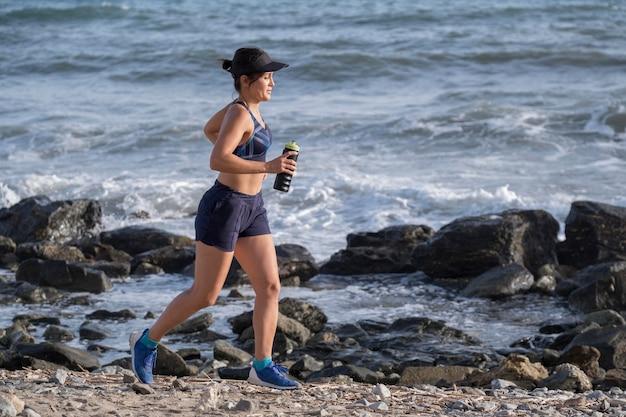 Женщина под высоким углом работает на берегу моря Бесплатные Фотографии