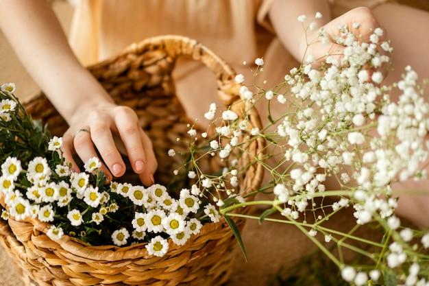 Alto angolo di donna con cesto di fiori primaverili Foto Gratuite