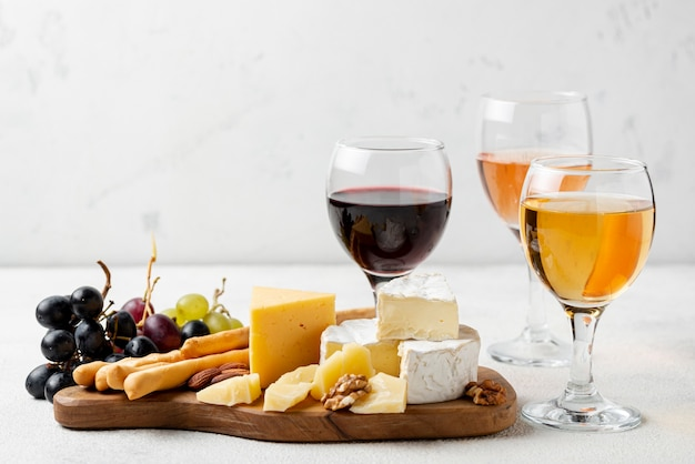 High angle wooden tray with cheese and wine for tasting Free Photo
