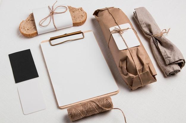 空白のメモ帳とラベルが付いた高角度で包まれたバゲットとパンのスライス 無料写真