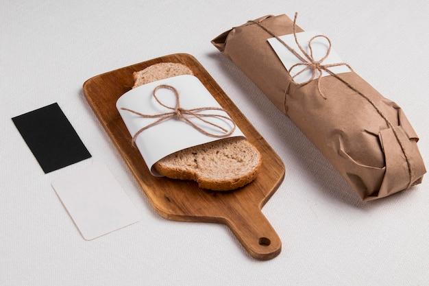 バゲットとまな板の上の高角度で包まれたパンのスライス 無料写真