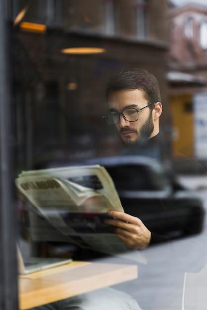 High angle young mal e reading newspaper Free Photo
