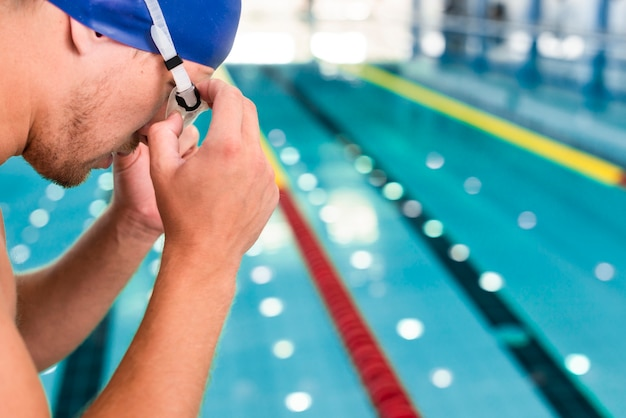 High angle young man putting goggles Free Photo