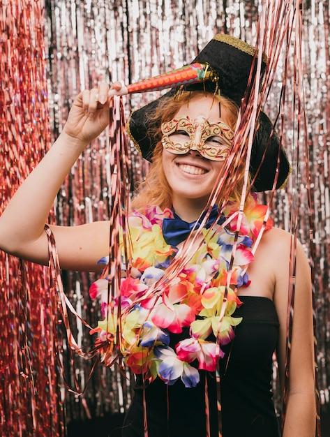 High angle young woman with mask at carnival party Free Photo