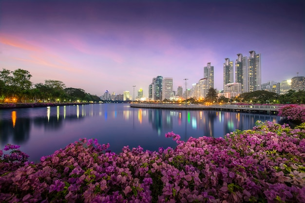 High business building behind the river in the park at beautiful night bangkok thailand Premium Photo
