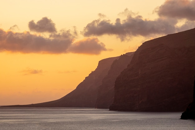 High cliffs by the sea at sunset Free Photo