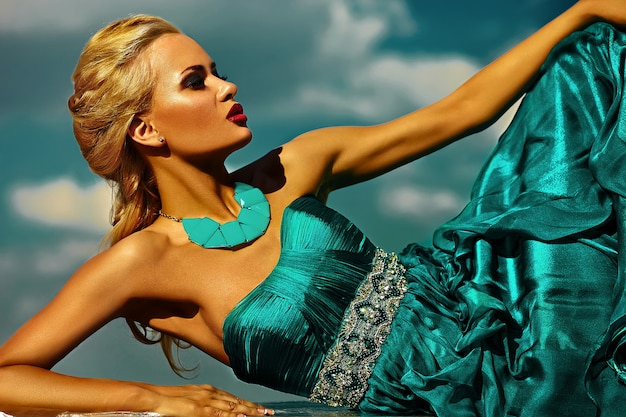 High fashion look.glamor beautiful sexy stylish blond young woman model with bright makeup  red lips with perfect sunbathed skin with jewelery outdoors in vogue style in evening long blue dress behind Free Photo