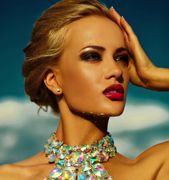 High fashion look.glamor closeup portrait of beautiful sexy stylish blond young woman model with bright makeup and red lips with perfect sunbathed clean skin with jewelery outdoors in vogue style Free Photo
