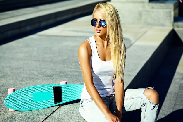 High fashion look.glamor stylish sexy beautiful young blond  model girl in summer bright casual hipster clothes with skateboard sitting in the street Free Photo