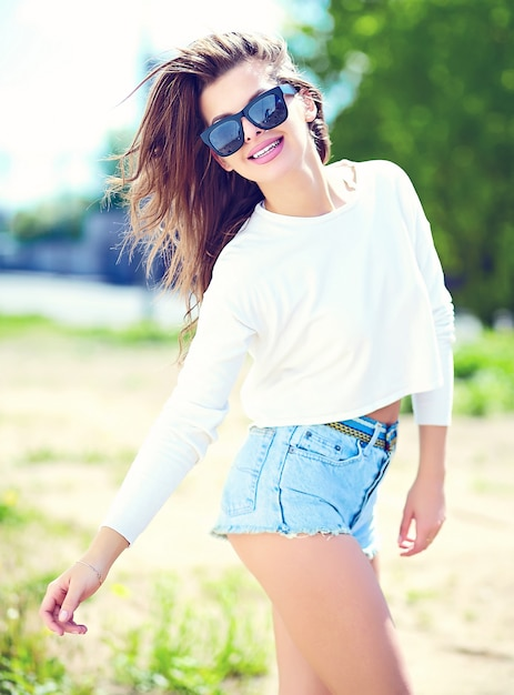 High fashion look.glamor stylish sexy smiling beautiful sensual young woman model in summer bright hipster cloth in jeans shorts in the street Free Photo