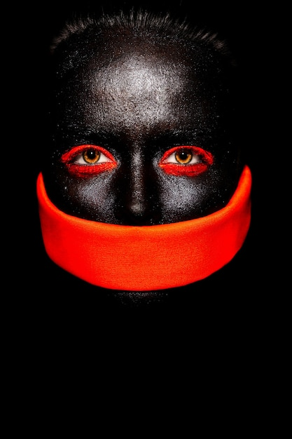 High fashion look.glamour fashion beautiful black american woman in black mask with orange bright makeup and orange material Free Photo