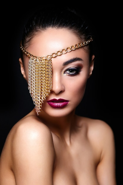 High fashion look.glamour fashion portrait of beautiful sexy brunette girl with bright makeup and golden accessories on eye Free Photo