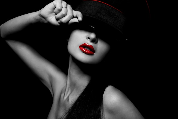 High fashion look.glamour portrait of beautiful sexy young female woman with red lips on black background with hat Free Photo