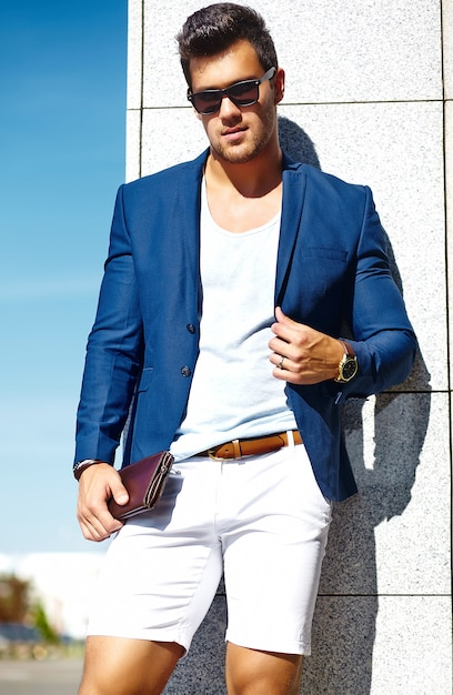 High fashion look.young stylish confident happy handsome businessman model man in blue suit clothes in the street in sunglasses behind sky Free Photo