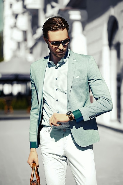 High fashion look.young stylish confident happy handsome businessman model  in suit cloth lifestyle in the street in sunglasses look his watch Free Photo