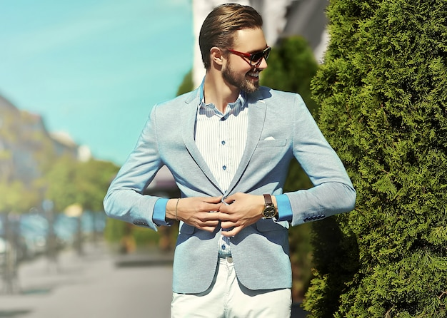 High fashion look.young stylish confident happy handsome businessman model in suit clothes lifestyle in the street in sunglasses Free Photo