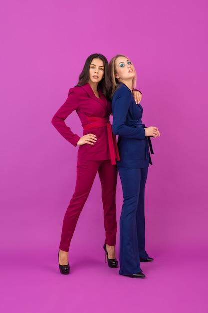 보라색과 파란색의 세련된 화려한 저녁 정장에 보라색 벽에 하이 패션 스타일 두 웃는 매력적인 여성, 친구가 함께 재미, 패션 트렌드 무료 사진