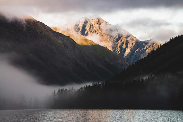 Высокий горный пик золота и много низких облаков над горным озером на восходе солнца. плотный туман над водой и лесом в золотой час. атмосферный высокогорный пейзаж ранним утром. альпийский расслабляющий пейзаж. Premium Фотографии