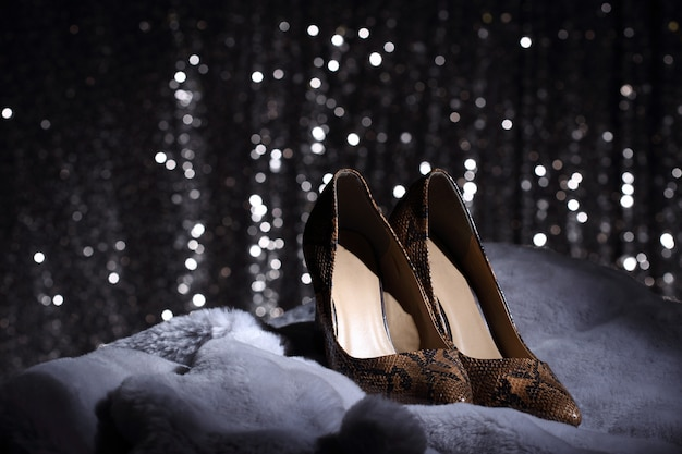 High heels shoes on fur and silver wallpaper Premium Photo