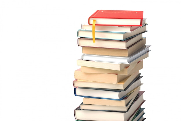High pile of different books isolated . red book with yellow bookmark on top of the pile background Premium Photo