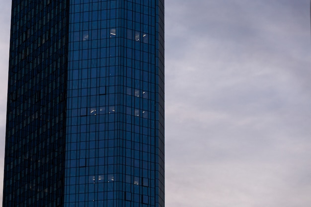 High-rise skyscraper in a glass facade under the cloudy sky in frankfurt, germany Free Photo