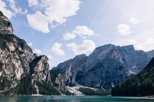 山の湖の周りの高いロッキー山脈。ブラーイエス湖。ドロミテ、イタリア。 Premium写真