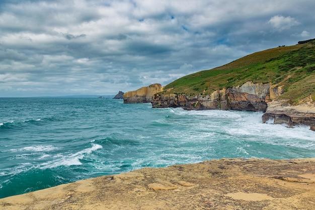 ニュージーランドのトンネルビーチでの高い砂浜の崖と太平洋の波 Premium写真