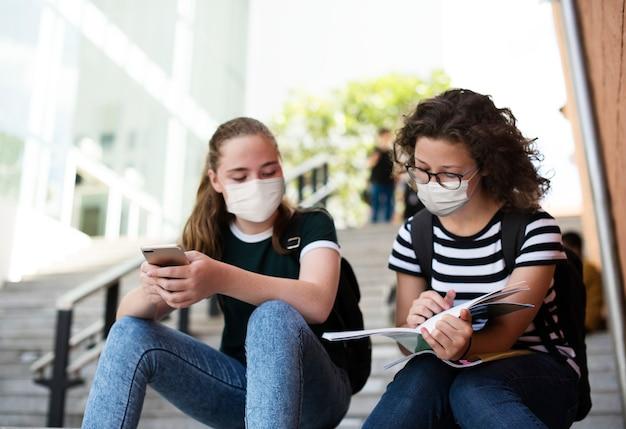 Studenti delle scuole superiori nella nuova normale che studiano sulle scale Foto Gratuite