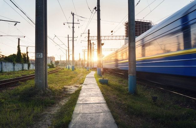 High speed passenger train in motion on railroad track at sunset Premium Photo