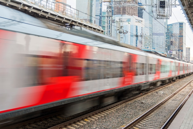High-speed train running in the city against the backdrop of skyscrapers. Premium Photo