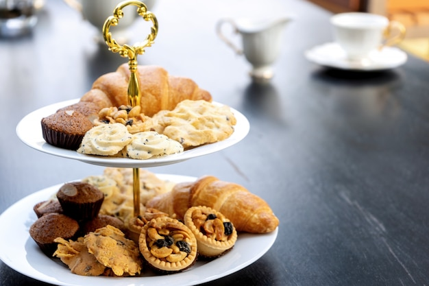 High tea set are on the black table Premium Photo