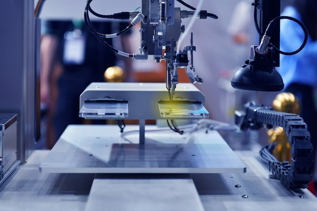 High technology and modern automatic robot for print circuit board (pcb)assembly machine during soldering or welding part or component at factory Premium Photo