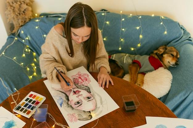 Artista di alta vista che dipinge un ritratto seduto accanto a un cane Foto Gratuite