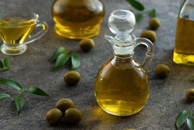 High view of bottles filled with olive oil on marble background Free Photo