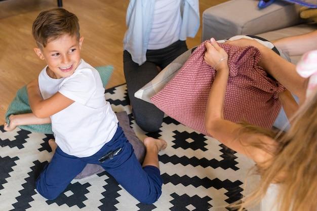 Высокий вид детей, играющих с подушками Бесплатные Фотографии