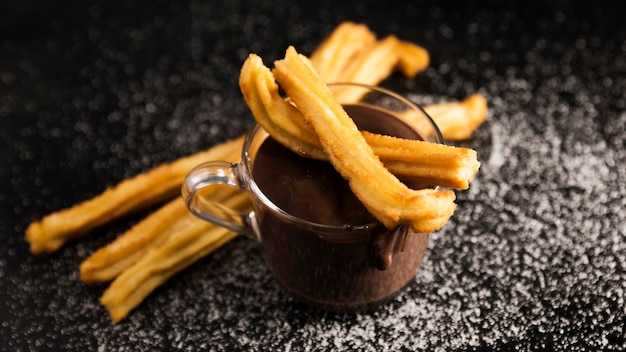 High view churros and cup of melted chocolate Free Photo