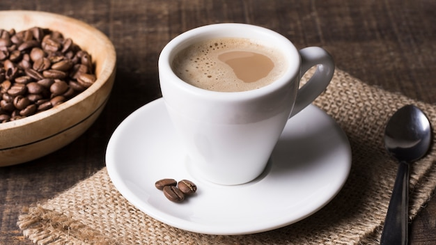 High view delicious coffee and coffee beans Free Photo