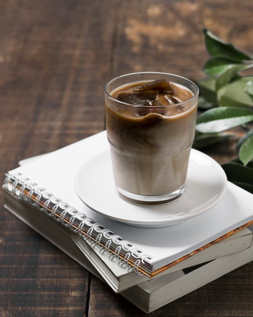 High view delicious coffee in cup on pile of notebooks Free Photo