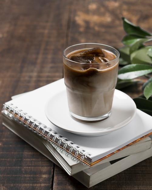 Высокий вид вкусный кофе в чашке на кучу тетрадей Premium Фотографии