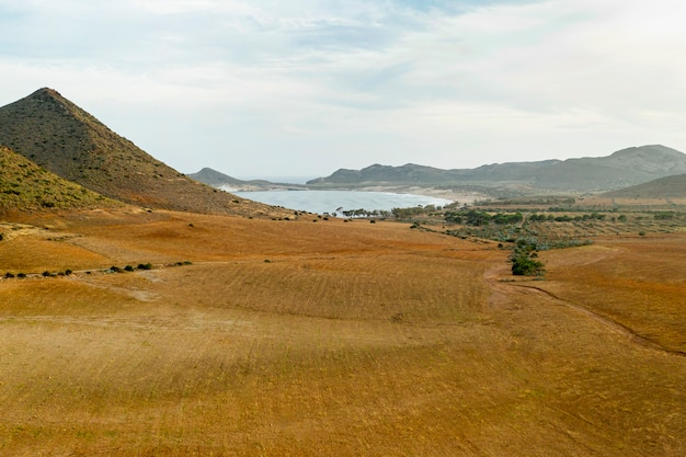 High view of dried field and mountains with lakes Free Photo