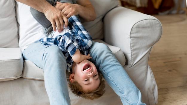Padre di alta vista che solletica bambino felice Foto Gratuite