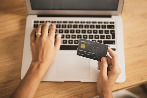 High view of laptop and credit card for shopping Free Photo