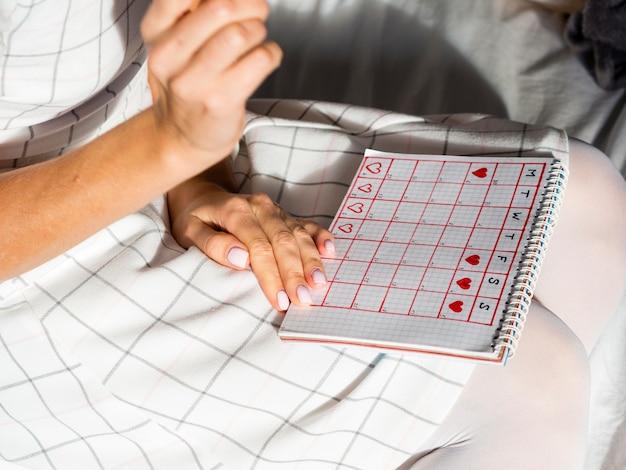 High view period calendar on a female lap | Free Photo