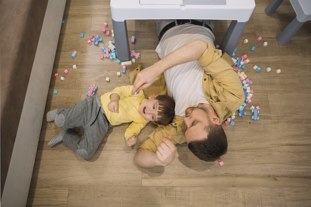 High view son and father laying under the table Free Photo
