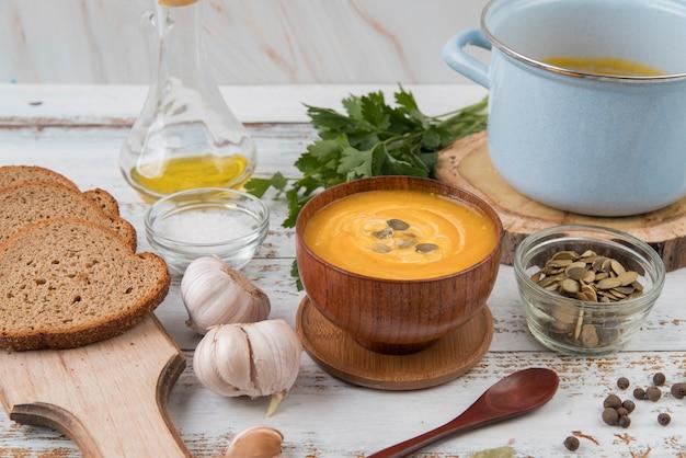 Высокий вид деревянный стол с супом и ломтиками хлеба Бесплатные Фотографии