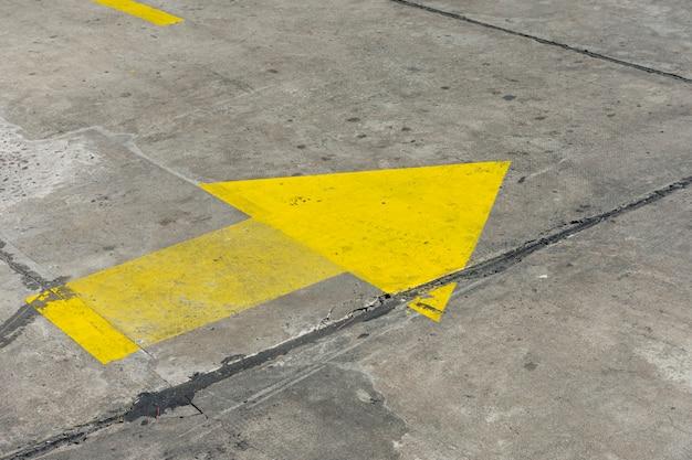Alta vista giallo freccia dipinta nelle strade Foto Gratuite
