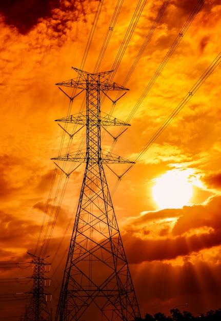 Высоковольтный электрический столб и линии электропередачи. опоры электричества на заходе солнца. сила и энергия. энергосбережение. высоковольтная сеточная вышка с проводным кабелем. золотое небо. Premium Фотографии