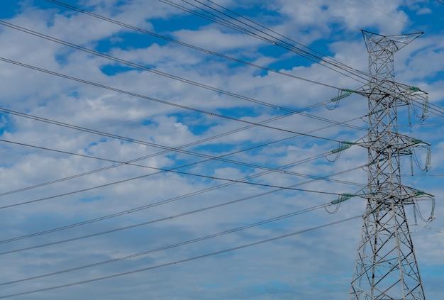 푸른 하늘과 구름에 대 한 고전압 전기 철 탑과 전선. 전기 철탑의 밑면. 와이어 케이블이있는 고전압 그리드 타워. 프리미엄 사진