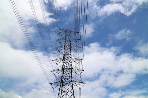 Полюс высокого напряжения, столб электричества с голубым небом и белым облаком. промышленное, технологическое и природное понятие. Premium Фотографии