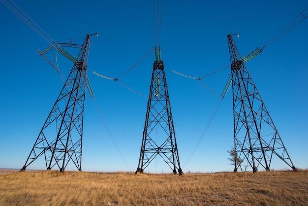Столбы высоковольтной линии электропередач в поле в голубом небе Premium Фотографии